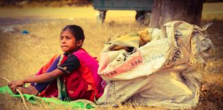 A poor girl sits with sack of waste, In India