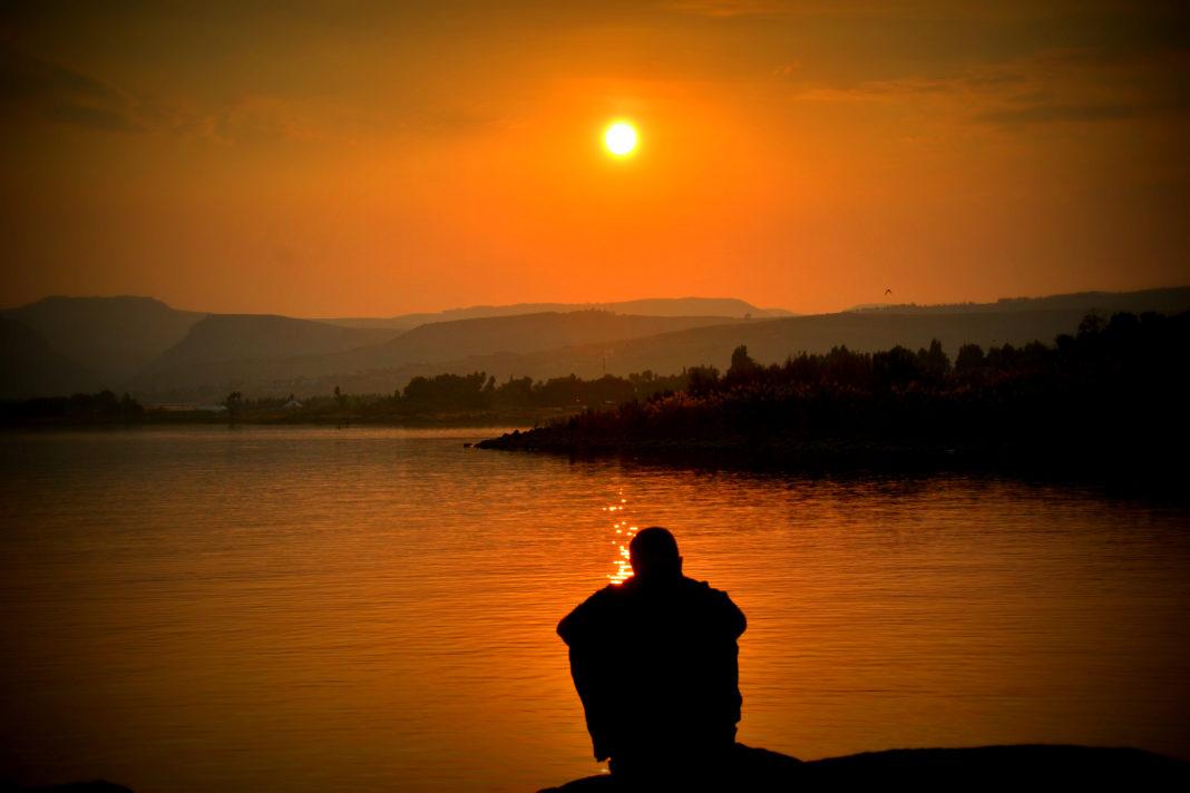 A traveler sitting and enjoying sunset