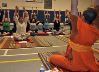 People performing Yoga under guidance of a yoga guru
