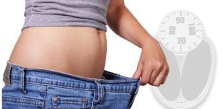 Slim woman's belly with over sized jeans