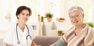 Nurse measuring blood pressure of senior woman at home. Looking at camera, smiling