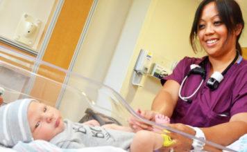 nurse examines a newborn